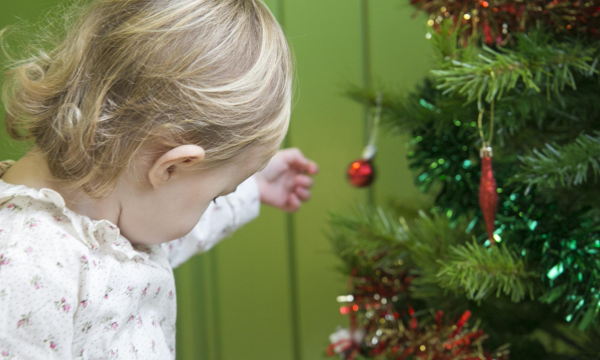 the child who does not like to be photographed looking at the christmas tree