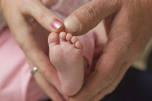 Tiny foot in parents hands make a heart
