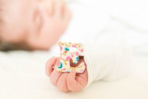 an imaged of Emily, a sleeping baby, clutching the letter E during an Oldham family photography session