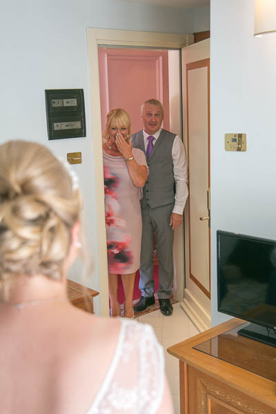 Mother and father of the bride get a first glimpse of their daughter ready to walk yup the aisle