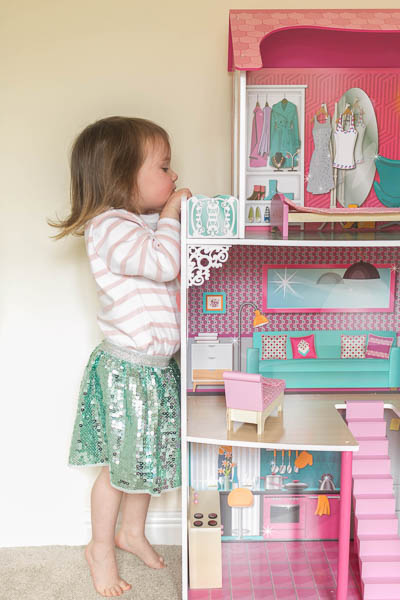 Toddler peeking over her dolls house as she plays